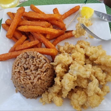 Cracked conch with sweet potato fries and peas and rice.