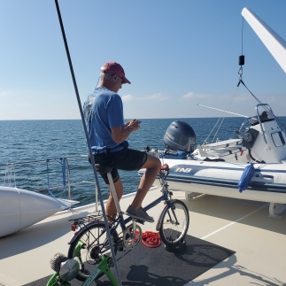 Scott is preparing to ride his bike while underway. Around his waist is his inflatable life jacket in case a big waves throws him off the boat!